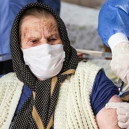 An elderly Iranian woman receives a vaccine shot. Urmia, Iran. Mar. 18, 2021. (Photo by Mojtaba Esmail Zad via Tasnim News Agency)
