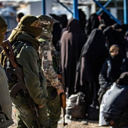 Kurdish fighters stand guard at Al-Hol camp which holds suspected relatives of Islamic State (IS) group militants, in Hasakeh governorate, Syria on Feb. 20, 2021. (Photo via Getty Images)