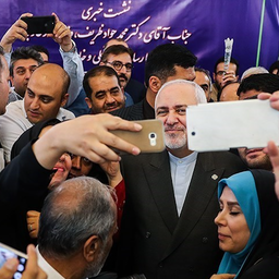 Iran's Foreign Minister Mohammad Javad Zarif poses for selfies with reporters as he leaves a press conference in Tehran on Aug. 5, 2019. (Photo by Hamed Malekpour via Tasnim News Agency)