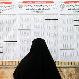 An Iranian woman looks at the list of city council candidates at a polling station in Tehran, Iran on June 18, 2021. (Photo via Tasnim News Agency)