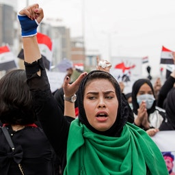 An Iraqi woman raises her fist during anti-government protests in Basra on Dec. 2, 2019. (Photo via Getty Images)