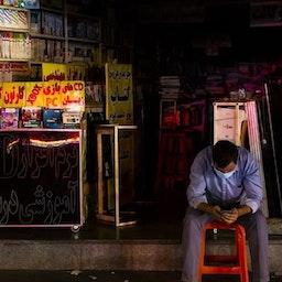 إيراني يجلس خارج متجره أثناء انقطاع التيار الكهربائي في طهران في 5 يوليو/تموز، 2021. (الصورة لمهدي دوراني عبر وكالة أنباء فارس)