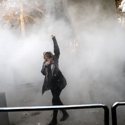 An Iranian woman raises her fist in the air amid a cloud of tear gas during a protest over economic hardship in Tehran, Iran on Dec. 30, 2017. (Photo via Getty Images)
