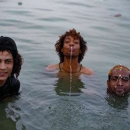 Sajjad Sami (middle) and his friends cool off in Shatt Al-Arab amid power cuts and tempurature rises in Iraq. July 7, 2021. (Photo by Azhar Al-Rubaie via Amwaj.media)