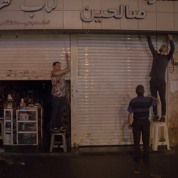 يكافح أصحاب المتاجر لإغلاق المصاريع الكهربائية يدويًا بسبب انقطاع التيار الكهربائي في طهران، إيران في 6 يوليو/تموز 2021 (تصوير محمد رضا بولاندي عبر وكالة أنباء إيسنا)