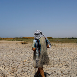 An Iranian fisherman passes the dried up Houralazim lagoon in Khuzestan province on July 4, 2021. (Photo by Amir Abidawi via ISNA News Agency)
