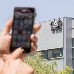 A woman uses her iPhone in front of the NSO Group's office in Herzliya, Israel on Aug. 28, 2016. (Photo via Getty Images)