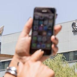 """إمرأة تستخدم هاتفها الآيفون قبالة مكتب مجموعة """"أن أس أو"""" في هرتسليا، إسرائيل. 28 أغسطس/ آب، 2016 (الصورة عبر غيتي إيماجز)"""