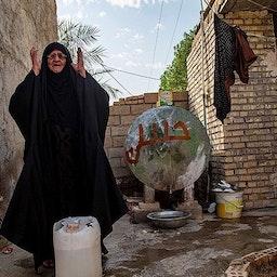 زنی عرب، در تقلا برای فراهمآوردن آب در زمان کمآبی شدید؛ حوالی اهواز، ایران، ۱۳ تیر ۱۴۰۰. (عکس از مهدی پدرامخو/ خبرگزاری تسنیم)