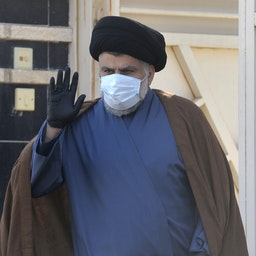 Iraqi cleric and politician Muqtada Al-Sadr in waves outside his home in the holy city Najaf, Iraq on Feb. 10, 2021. (Photo via Getty Images)