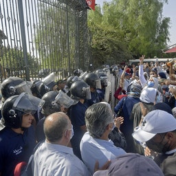 Tunisian security forces hold back protesters outside the parliament building in Tunis on July 26, 2021. (Photo via Getty Images)