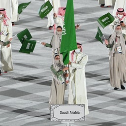 Saudi judoka Tahani Al-Qahtani (L) leads her country's delegation at the Tokyo Olympics opening ceremony. Jul. 23, 2021. (Photo via Getty Images)