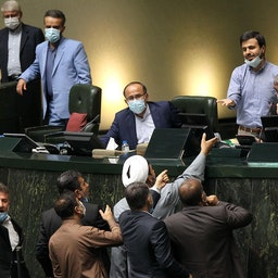 Iranian lawmakers surround the podium during a parliamentary session in Tehran on 28 July 2021. (Photo via  ICANA news agency)