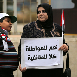 """An Iraqi woman carries a placard which reads """"Yes to citizenship, no to sectarianism"""" during an anti-corruption demonstration in Baghdad on Jan. 22, 2016. (Photo via Getty Images)"""