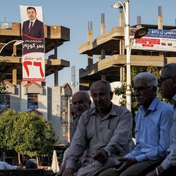 Men sit together while displayed on a nearby building is an electoral banner for the Oct. 10 parliamentary elections in Zakho, Iraq on Oct. 5, 2021. (Photo via Getty Images)