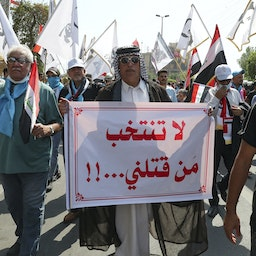 """An Iraqi man carries a placard which reads """"Don't vote for those who killed us"""" during a demonstration in Baghdad, Iraq on Oct. 1, 2021. (Photo via Getty Images)"""