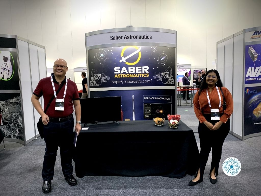 Dandelions team in front of Saber booth