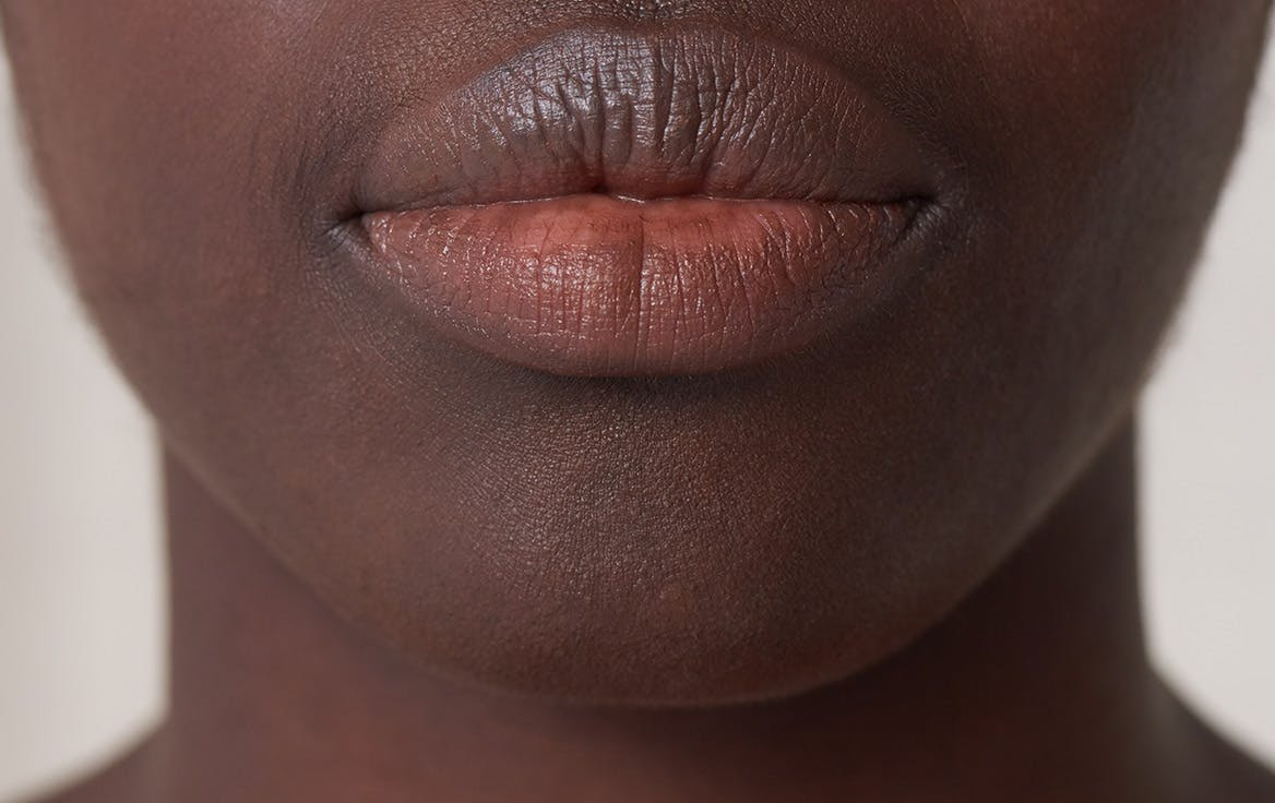 Close up photograph of woman's lips with visible mustache hairs