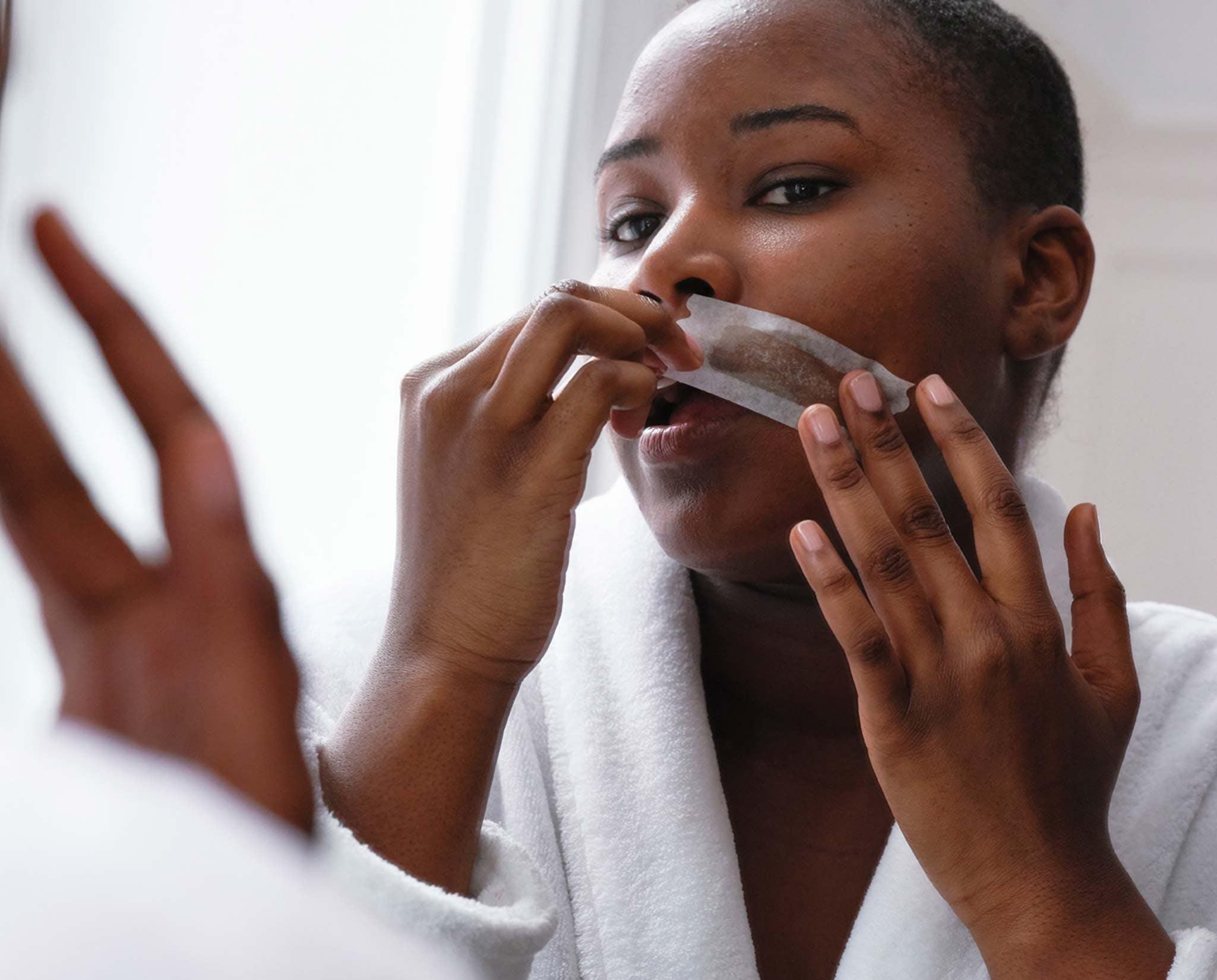 Woman pressing Flamingo Face Wax Strip into upper lip hair