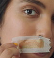 Woman with face wax strip applied to upper lip.