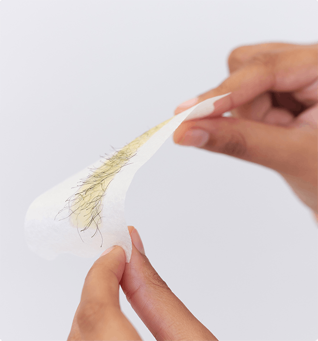 Woman holding pubic wax strip post waxing.