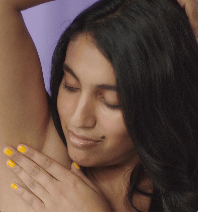 Woman touching armpit.