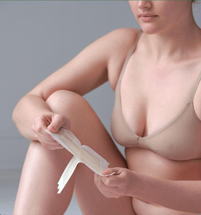 Woman pulling apart body wax strip.