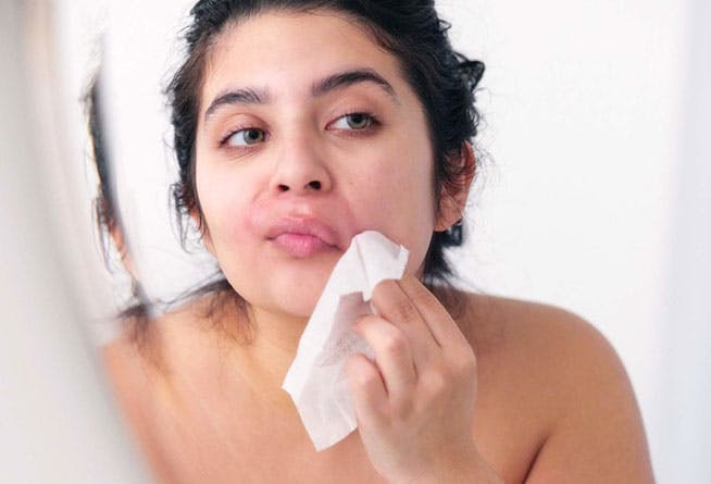 Woman removing wax with post wax cloth.