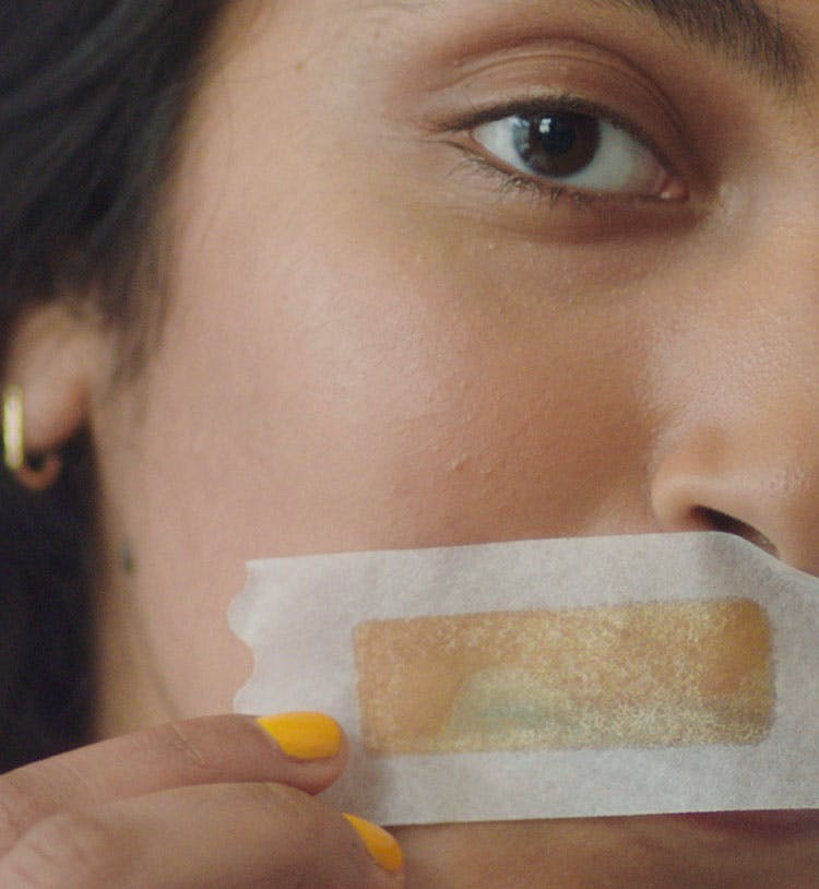 Woman holding face wax strip to upper lip.