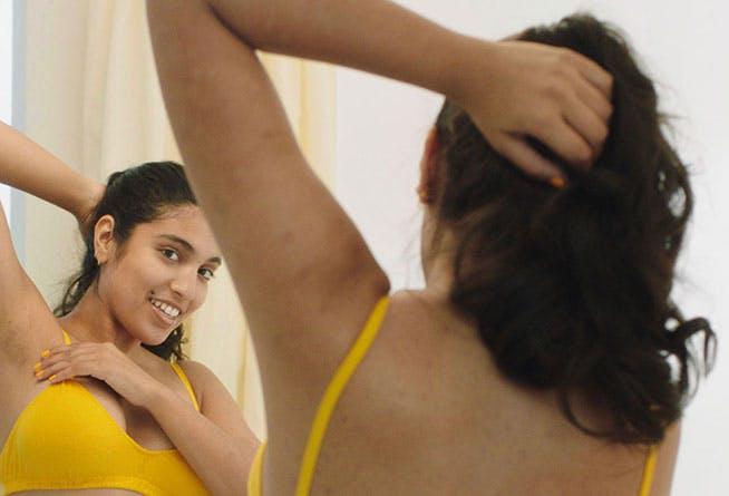 Woman looking in mirror post wax.