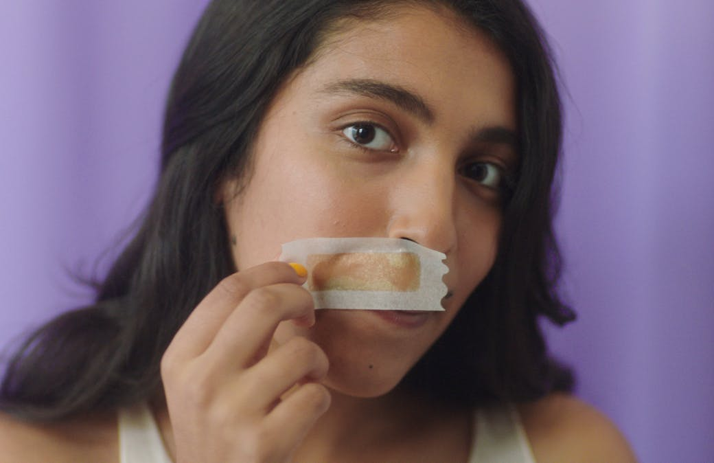 Woman holding wax strip against upper lip