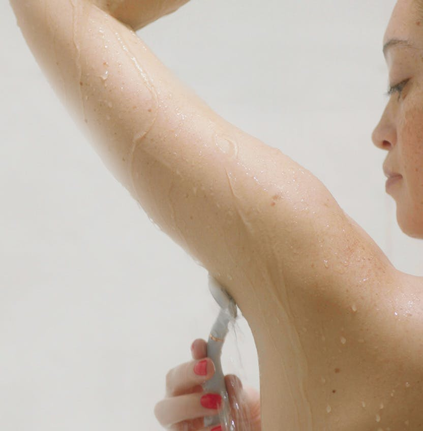Woman shaving in the shower