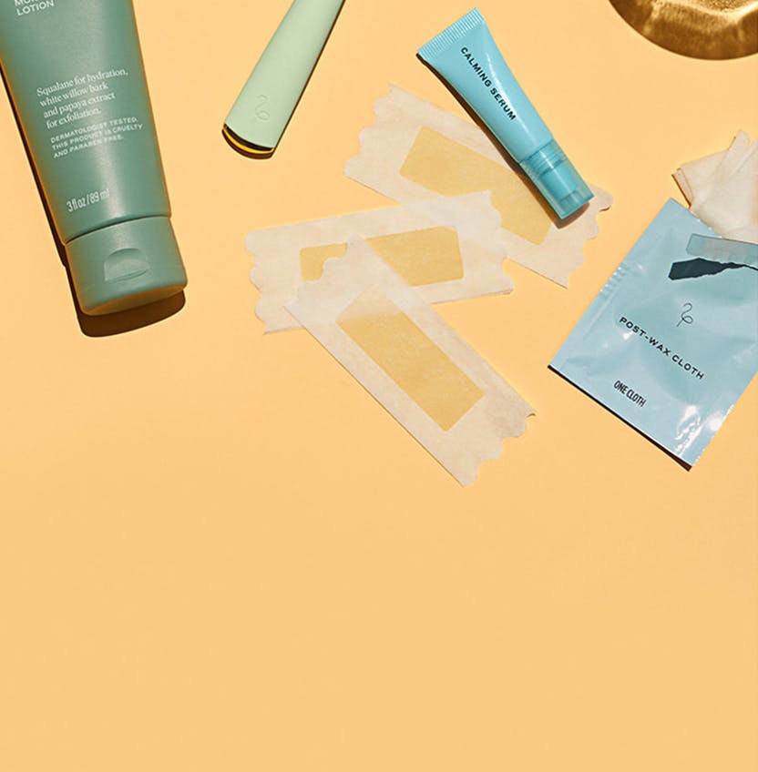 Body lotion, razor, and wax strips on a yellow background