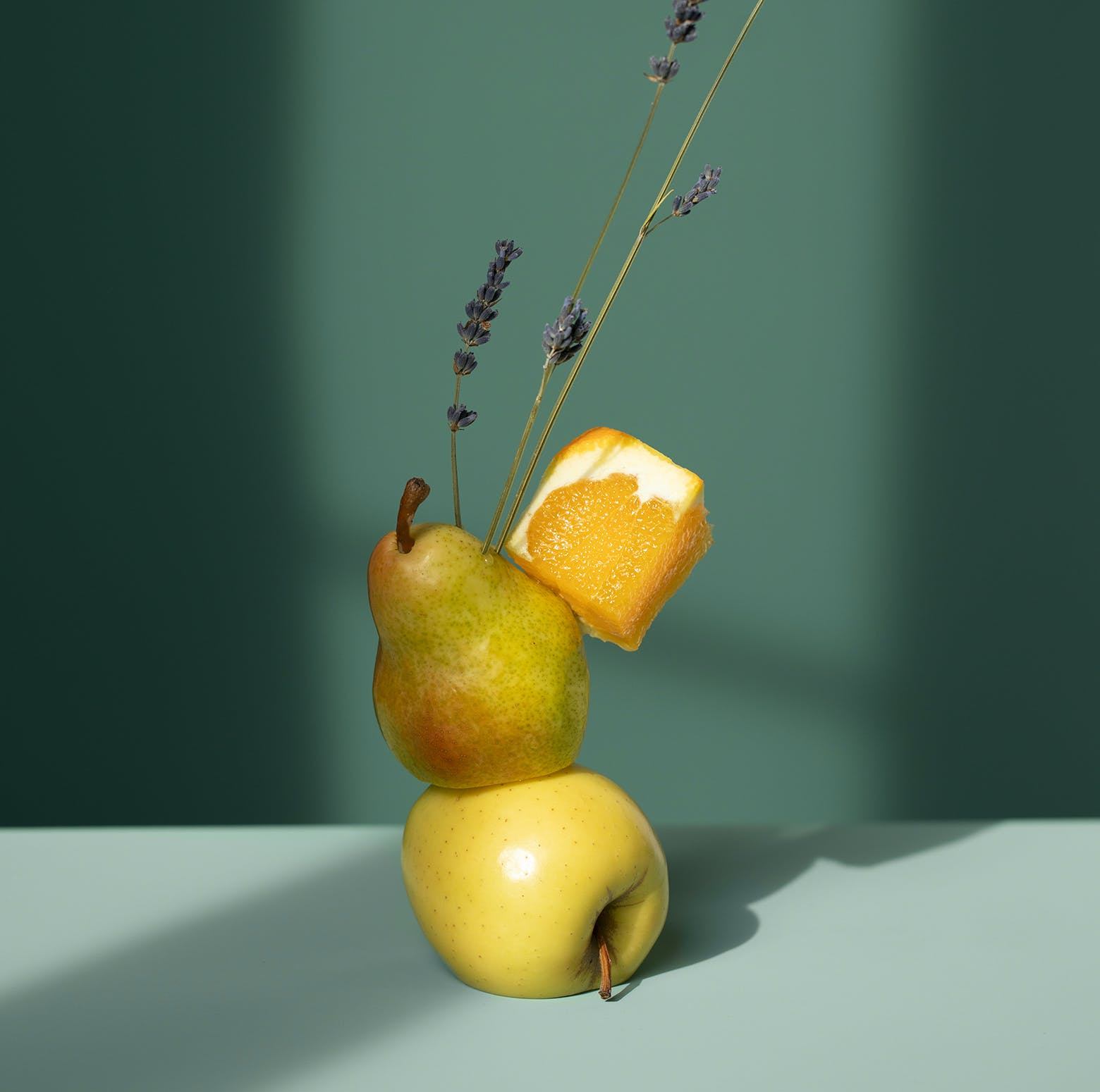 Pears stacked with a orange slice and lavender extending upwards