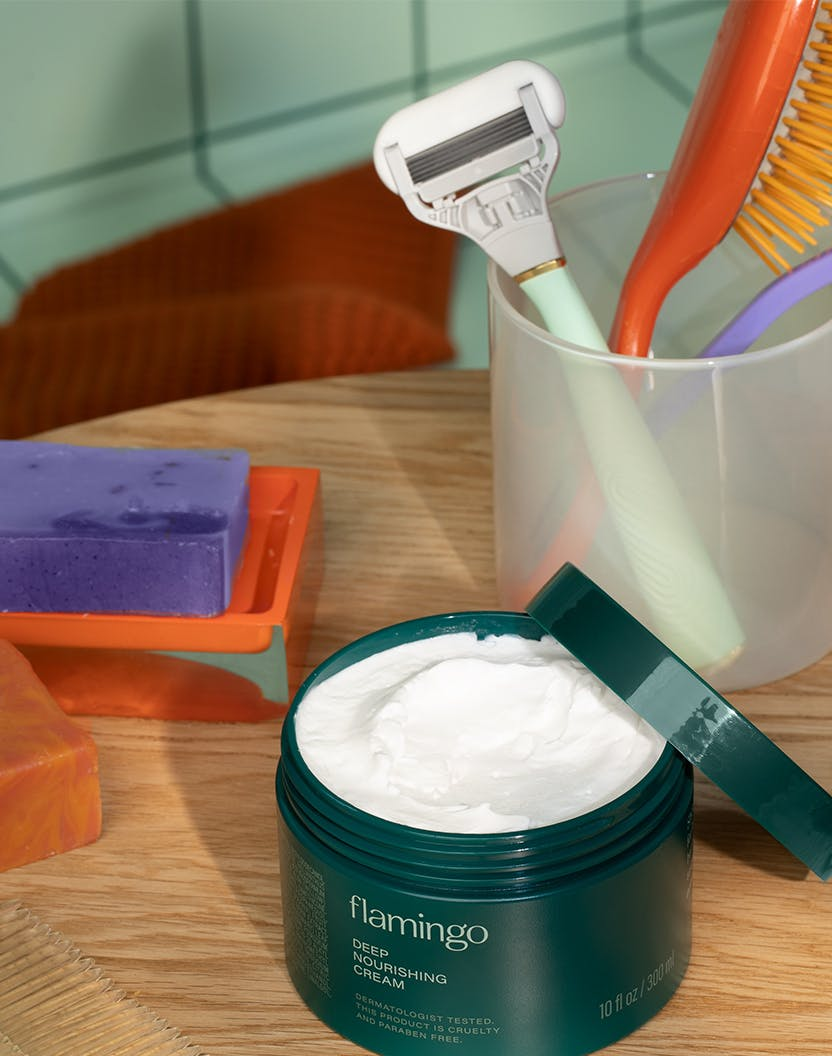 Deep nourishing cream in front of razor in a cup on a table