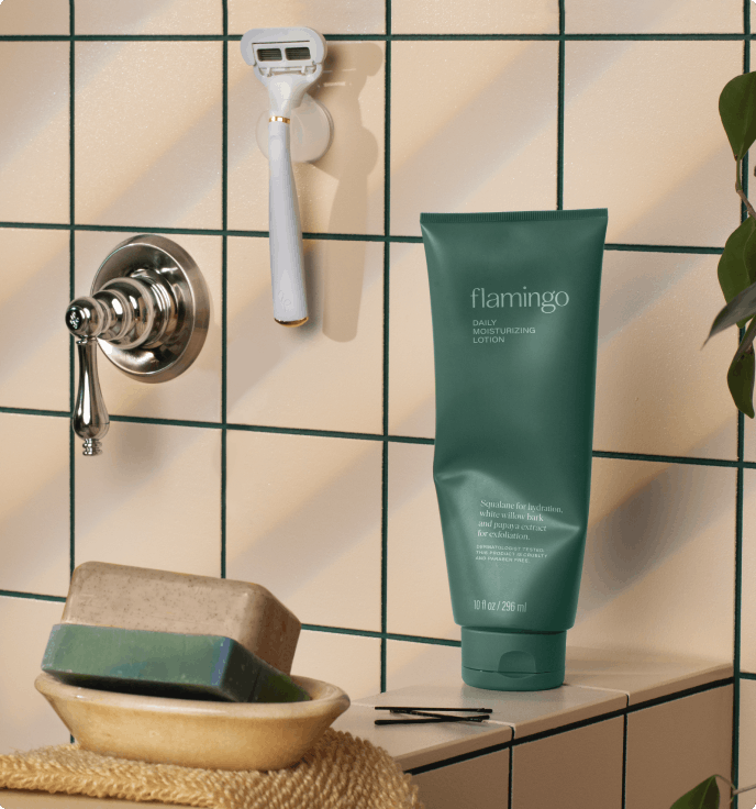 Daily moisturizing lotion on the side of a bathtub near a razor and soap