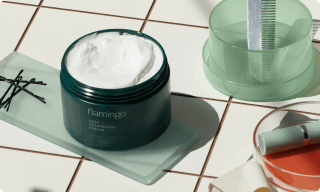 Deep nourishing cream on a bathroom counter surrounded by other beauty products