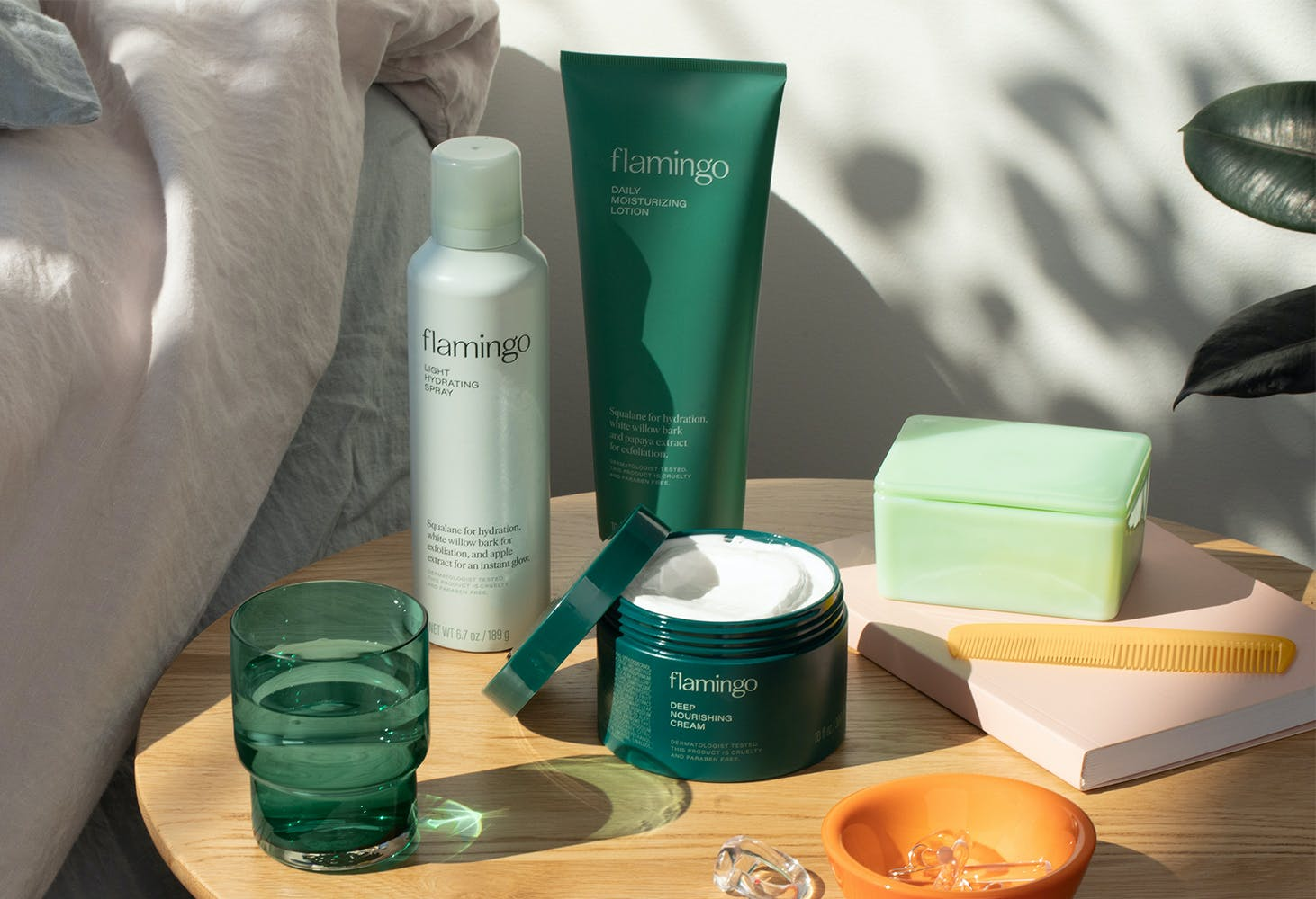Light hydrating spray, daily moisturizing lotion, and deep nourishing cream on a bed side table