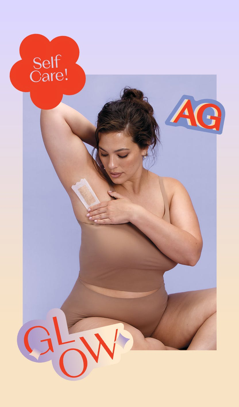 Ashley Graham applying a wax strip to her armpit with bright stickers around the photo
