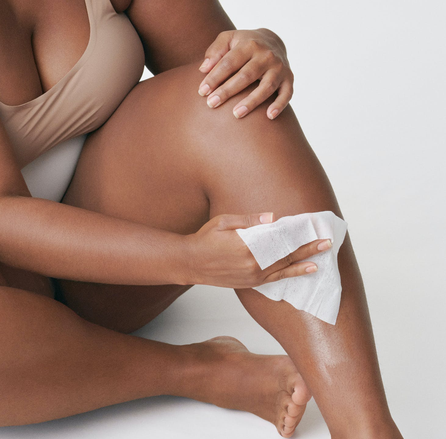 Woman removing excess wax with post wax cloth.