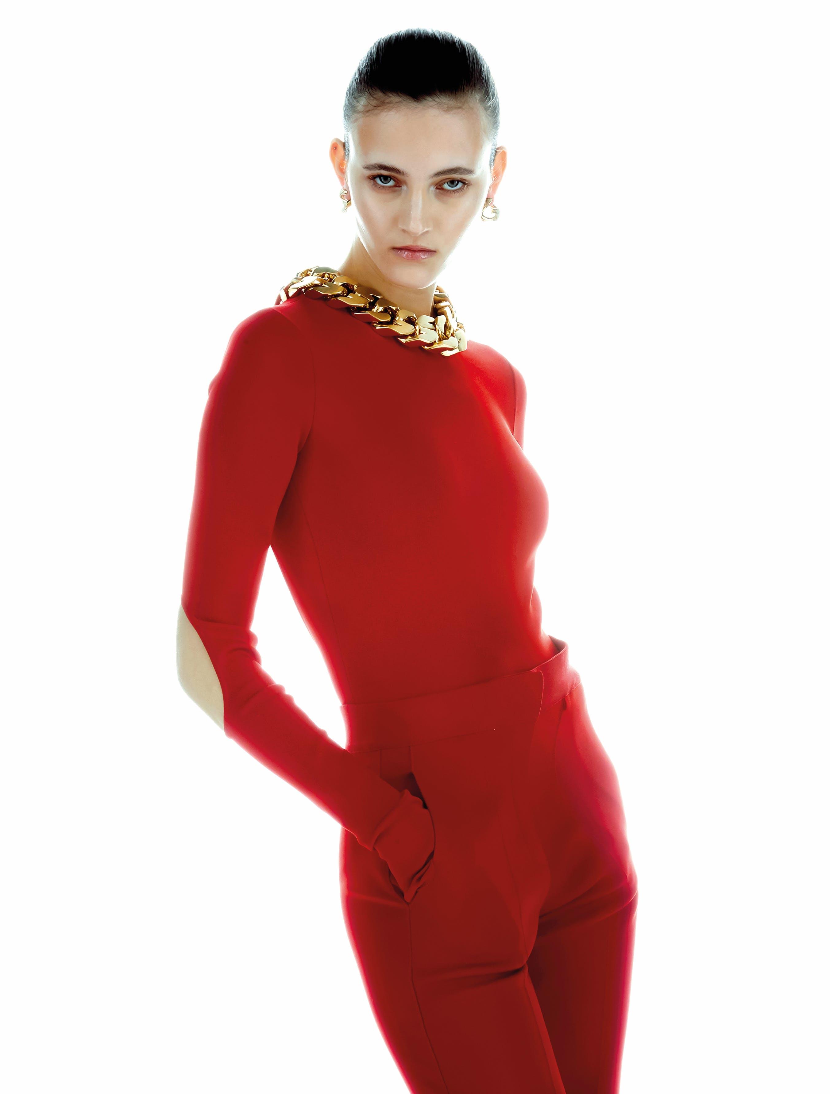 """Body di tessuto tecnico con cut out, pantaloni di cotone a vita alta, orecchini e collana """"G Chain"""" in ottone, GIVENCHY."""