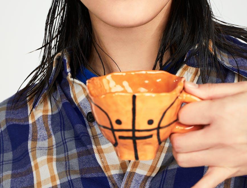 Modella orientale ssorseggia da una tazzina da tè con la forma di una palla da basket