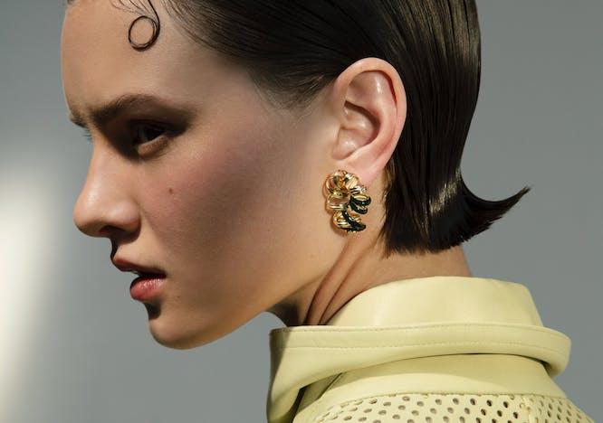 Modella indossa un paio di orecchini in oro giallo