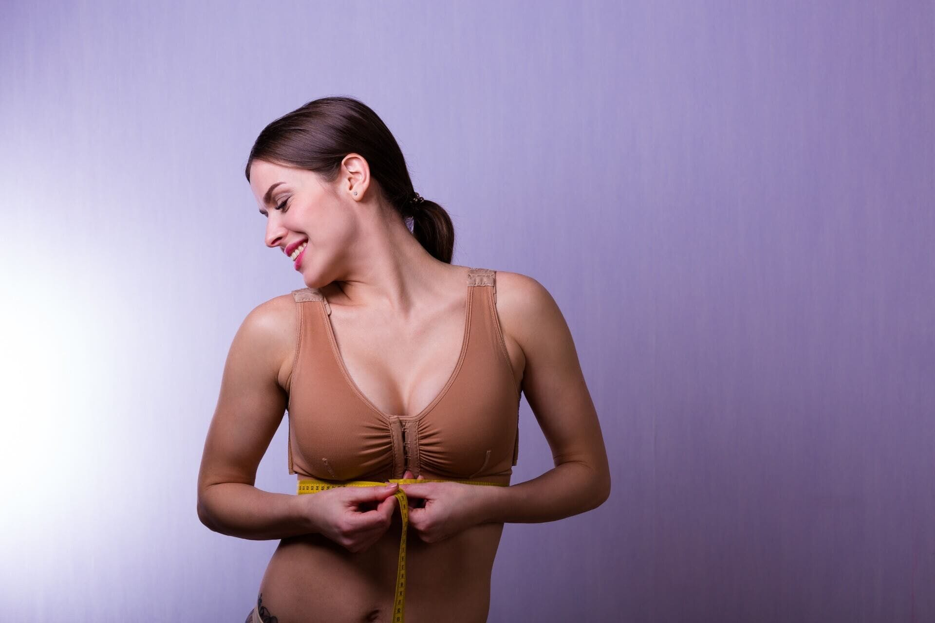 Woman smiling and wrapping breast with love metric