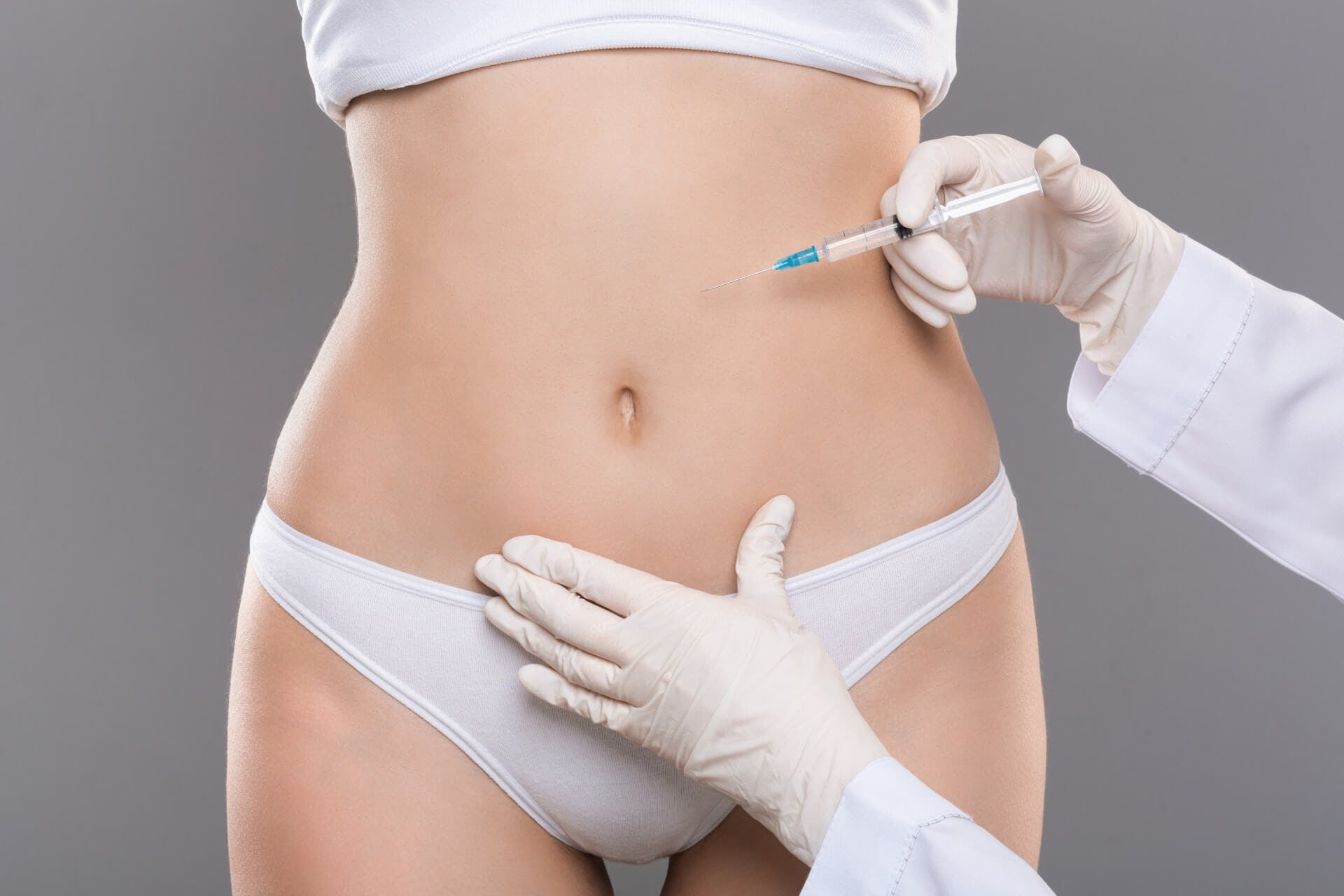 Doctor applying injection to woman's belly