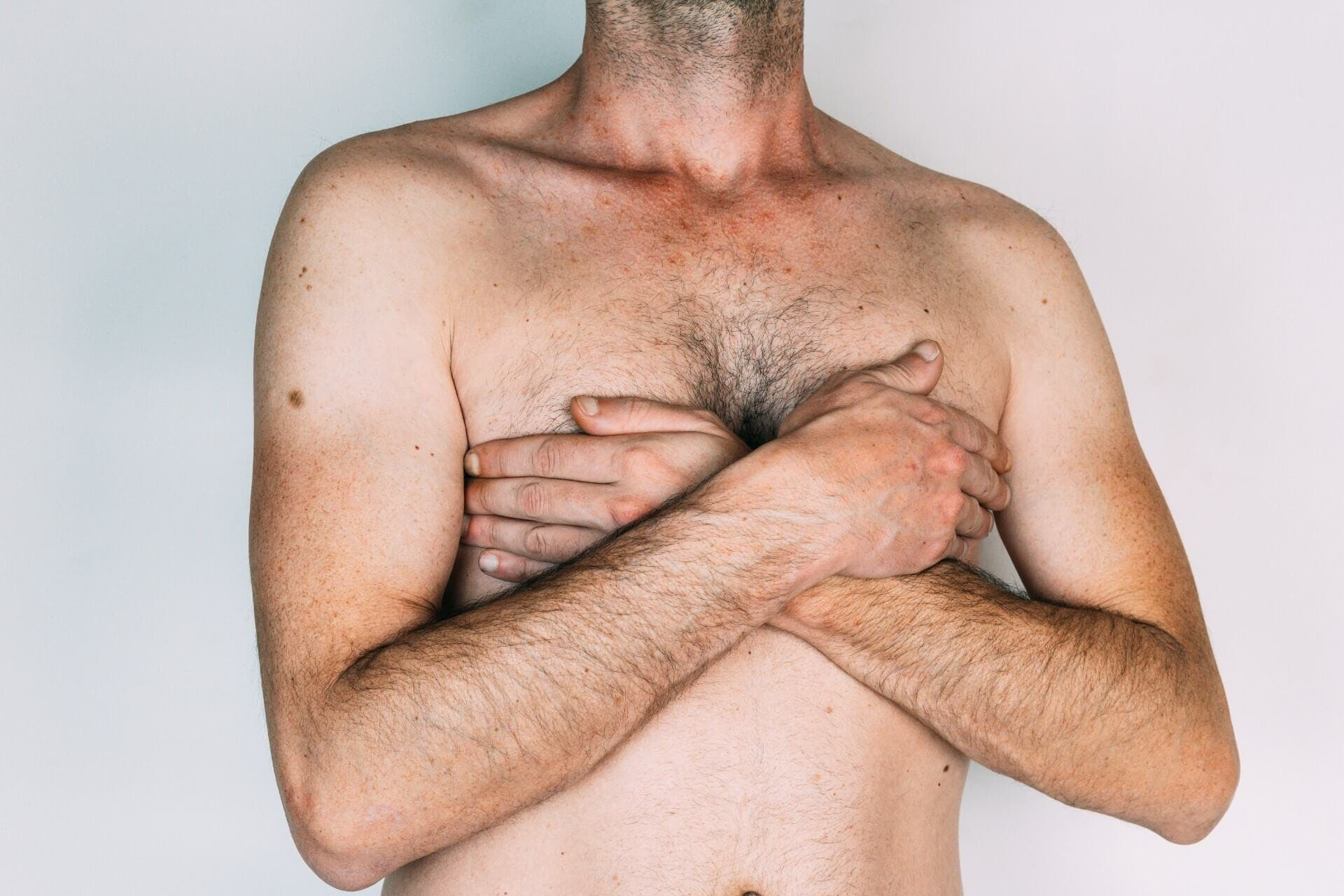 Man covering his chest with his hands