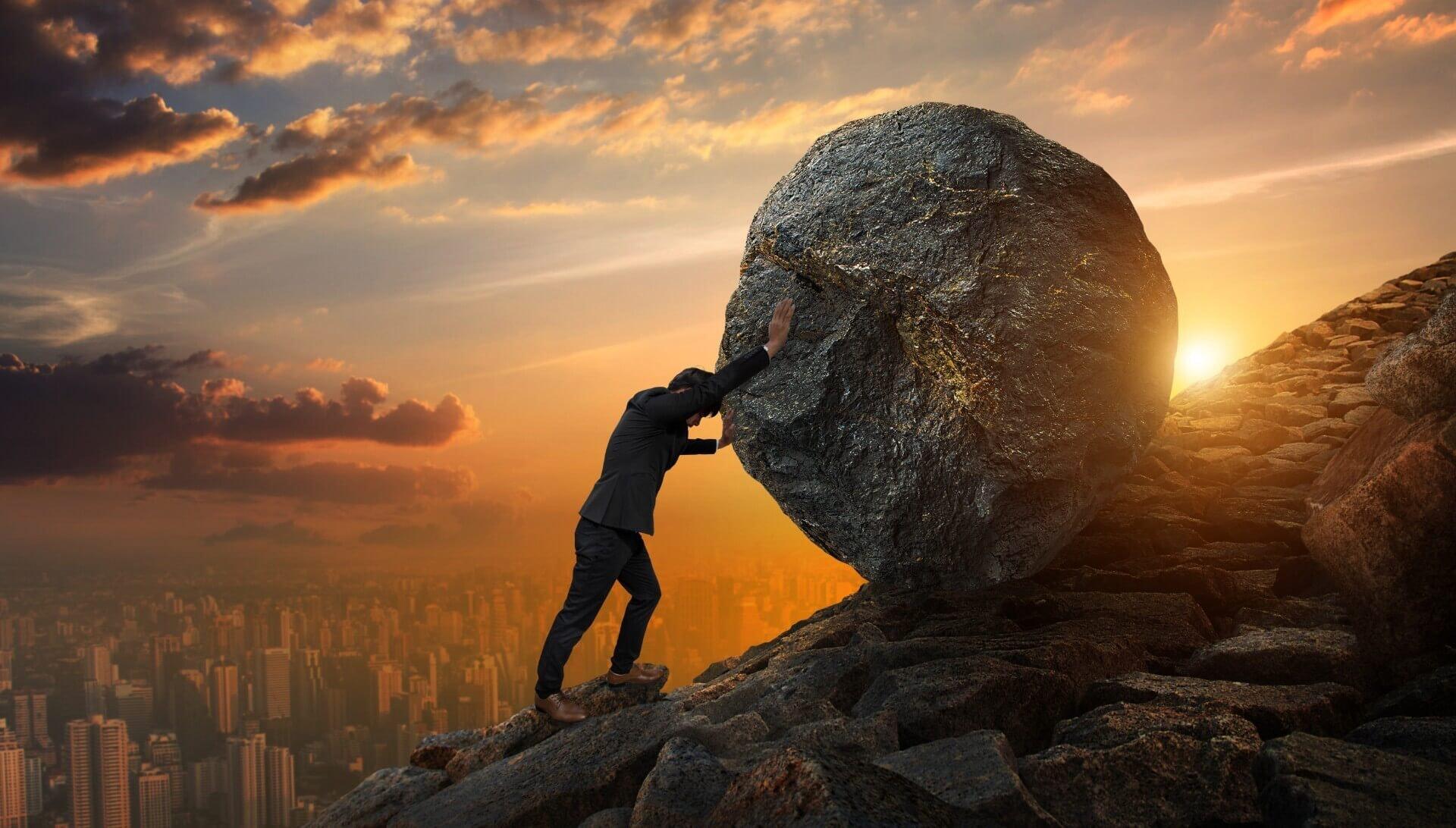 man holding a big rock