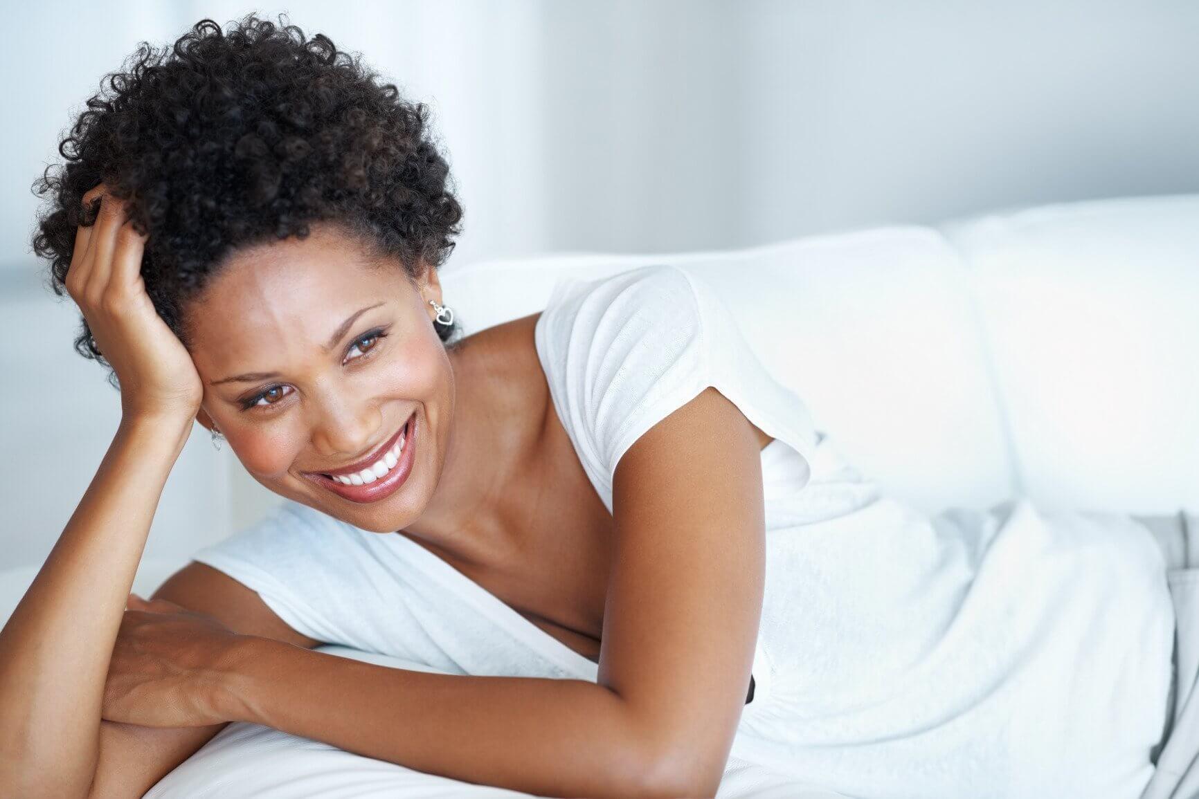 woman smiling on white sofa