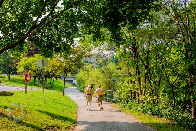 Two shirtless men jogging on a trail in a park