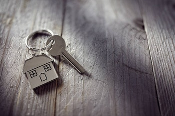 A key to a new home on a weathered wood surface